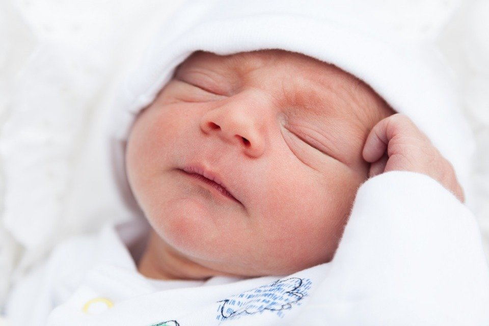 Newborn baby sleeping with hand propped against head.