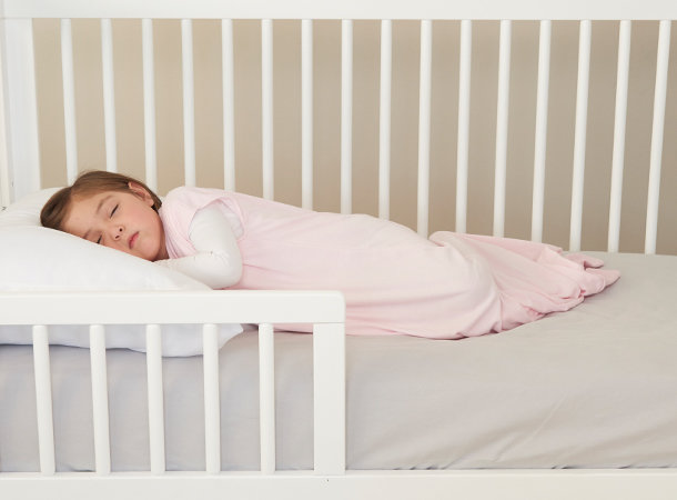 4 year old girl in pink sleepsack napping in white crib