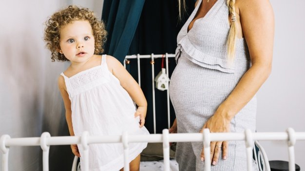 girl in white dress standing on bed after transitioning from crib with pregnant mom beside her