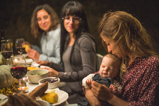 women and sleeping baby sitting at holiday dinner table