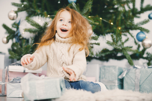 girl with red hair sitting beside Christmas tree with presents