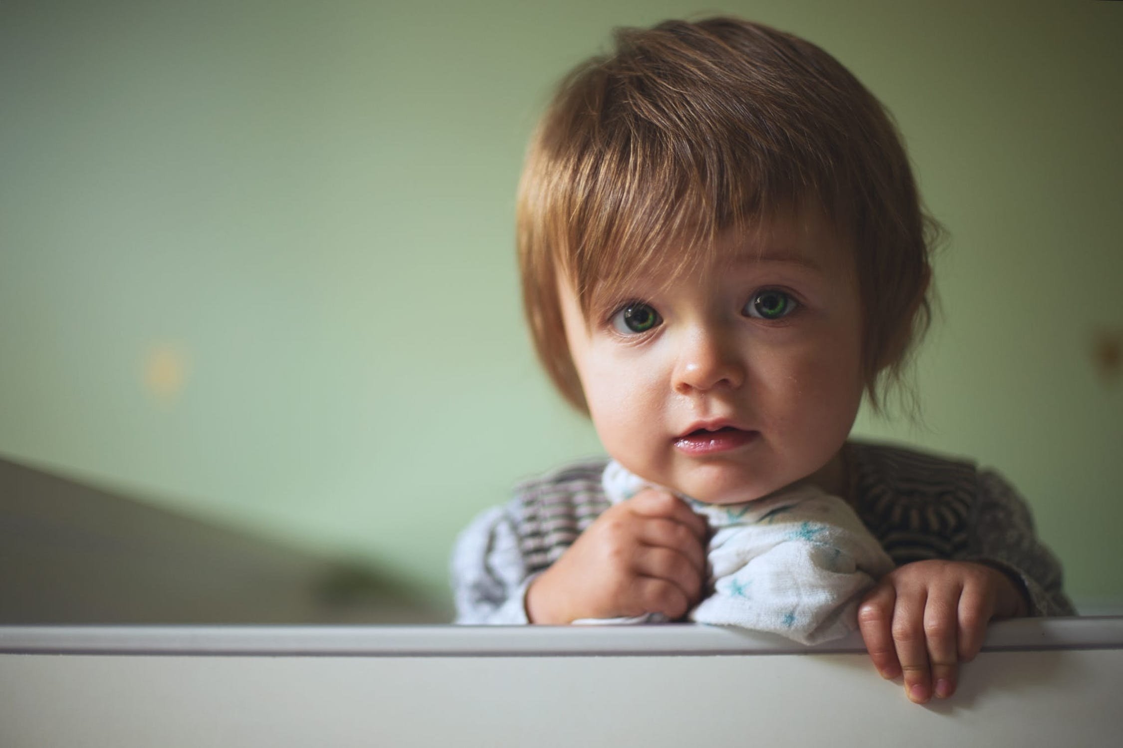 child who can't sleep standing up in crib holding blanket