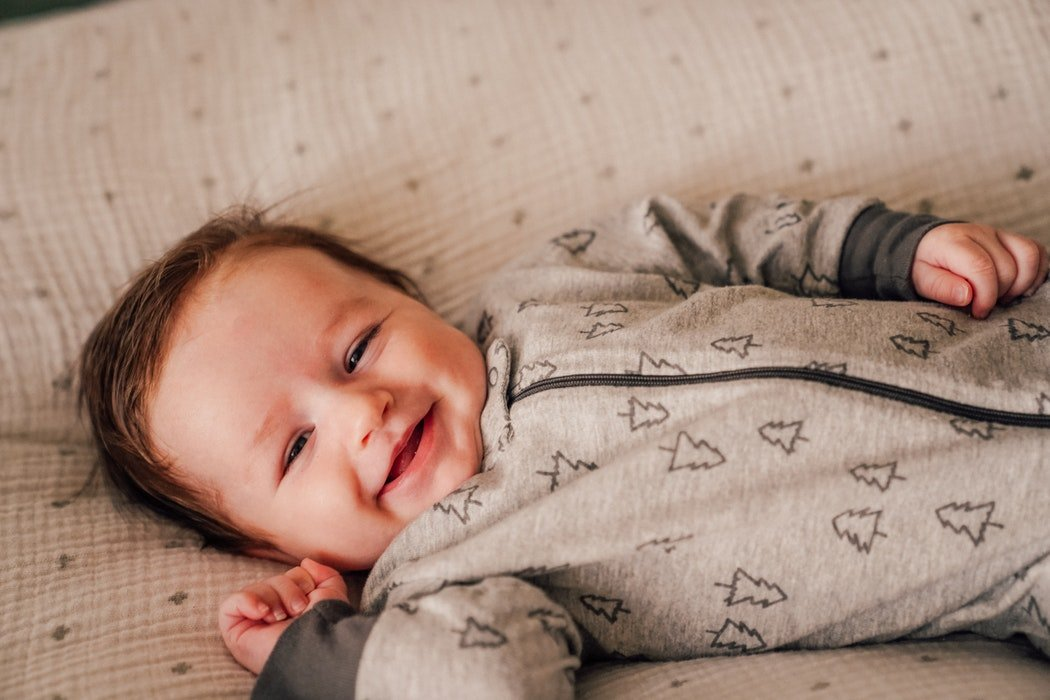 Happy baby lying on bed in grey jumpsuit with tree outlines