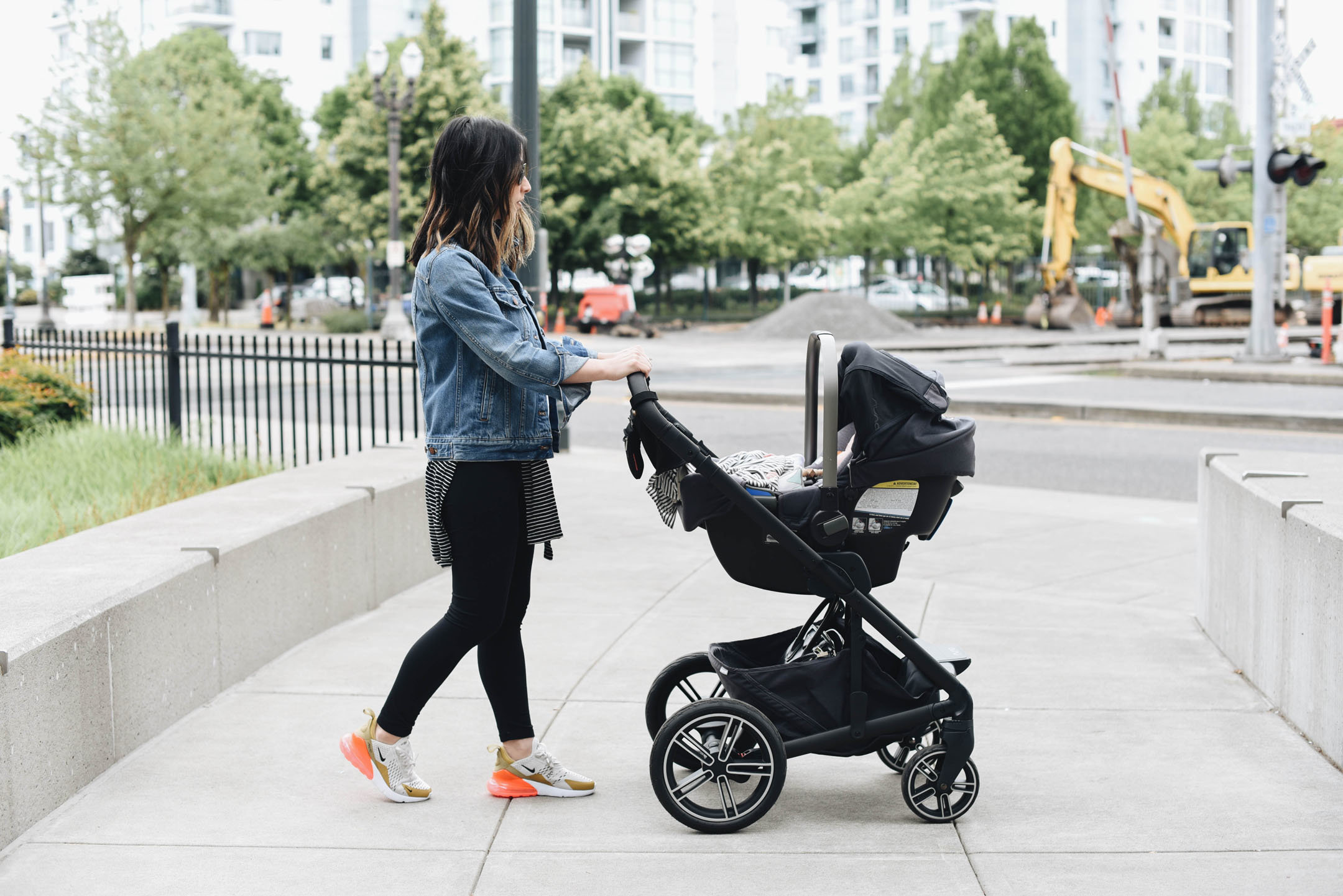 Woman pushing nuna Mixx2 stroller in the city near construction site