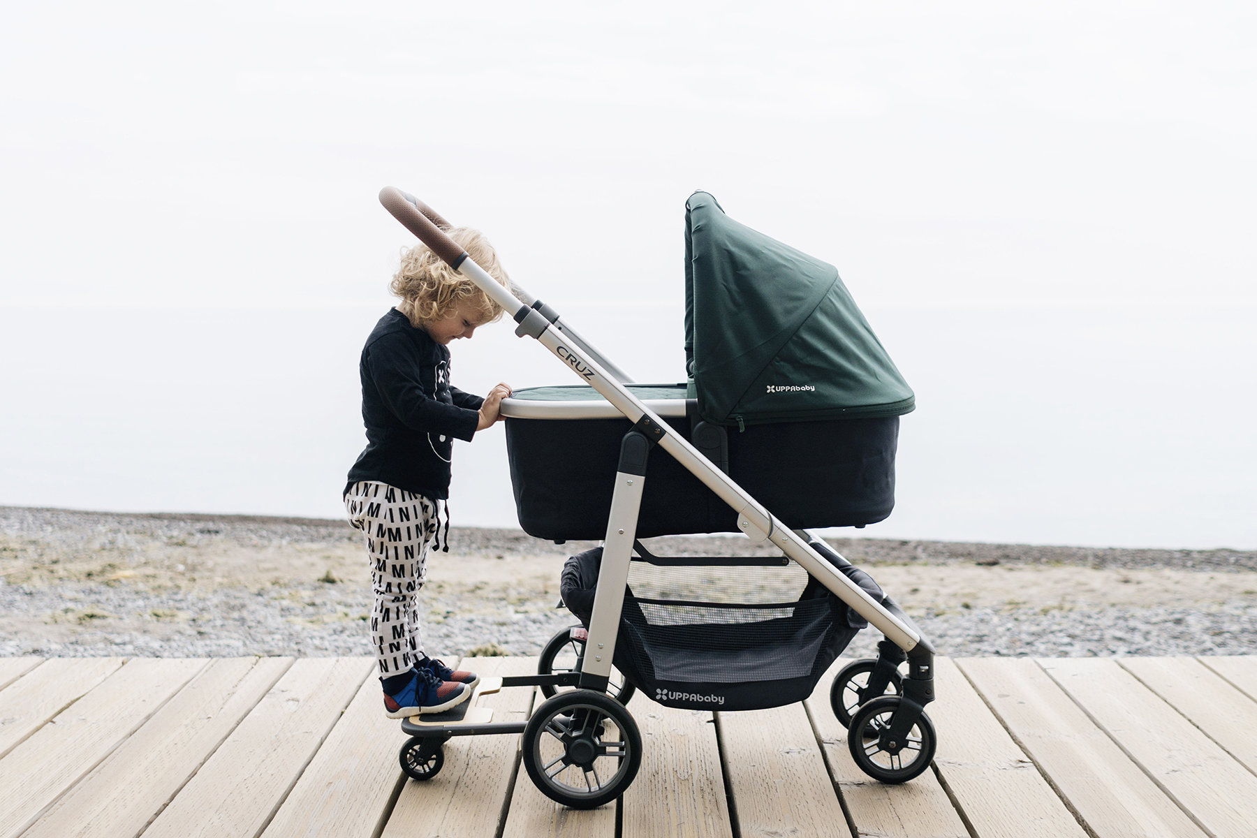 Kid standing on base of UPPAbaby Vista stroller with bassinet