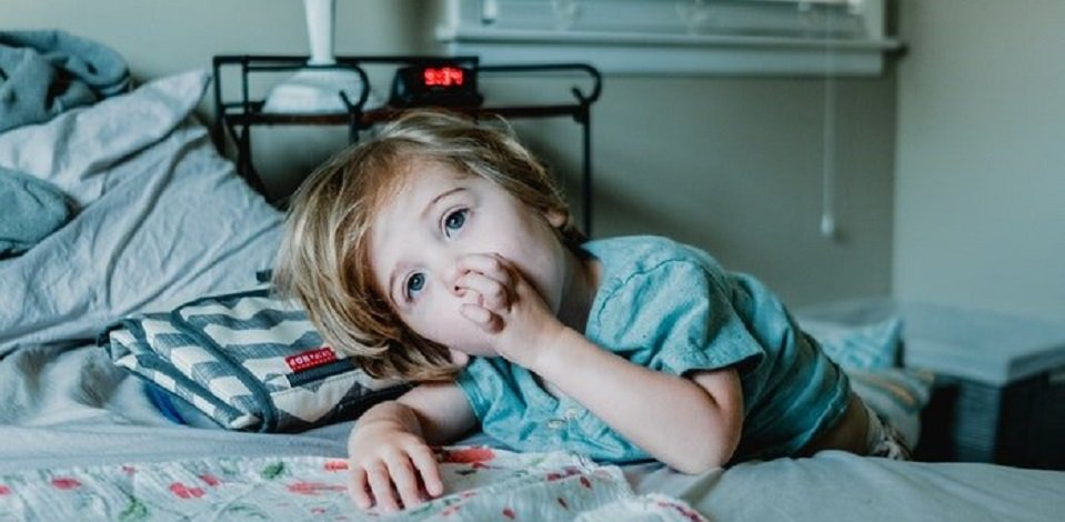 Young child sucking thumb while leaning against bed with alarm clock