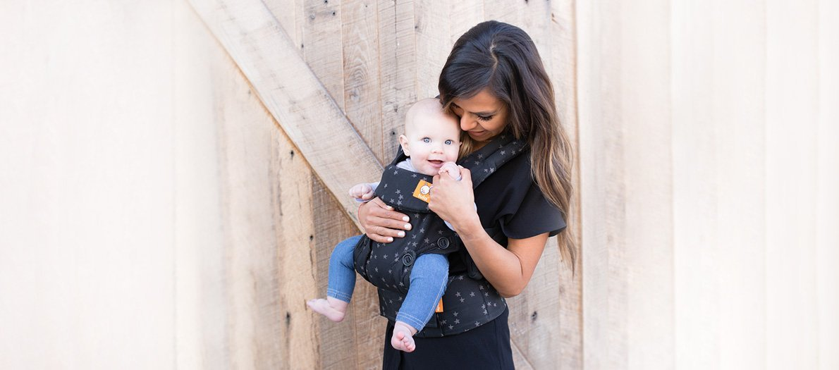 Mom wearing baby in soft structured carrier from Tula by wooden fence