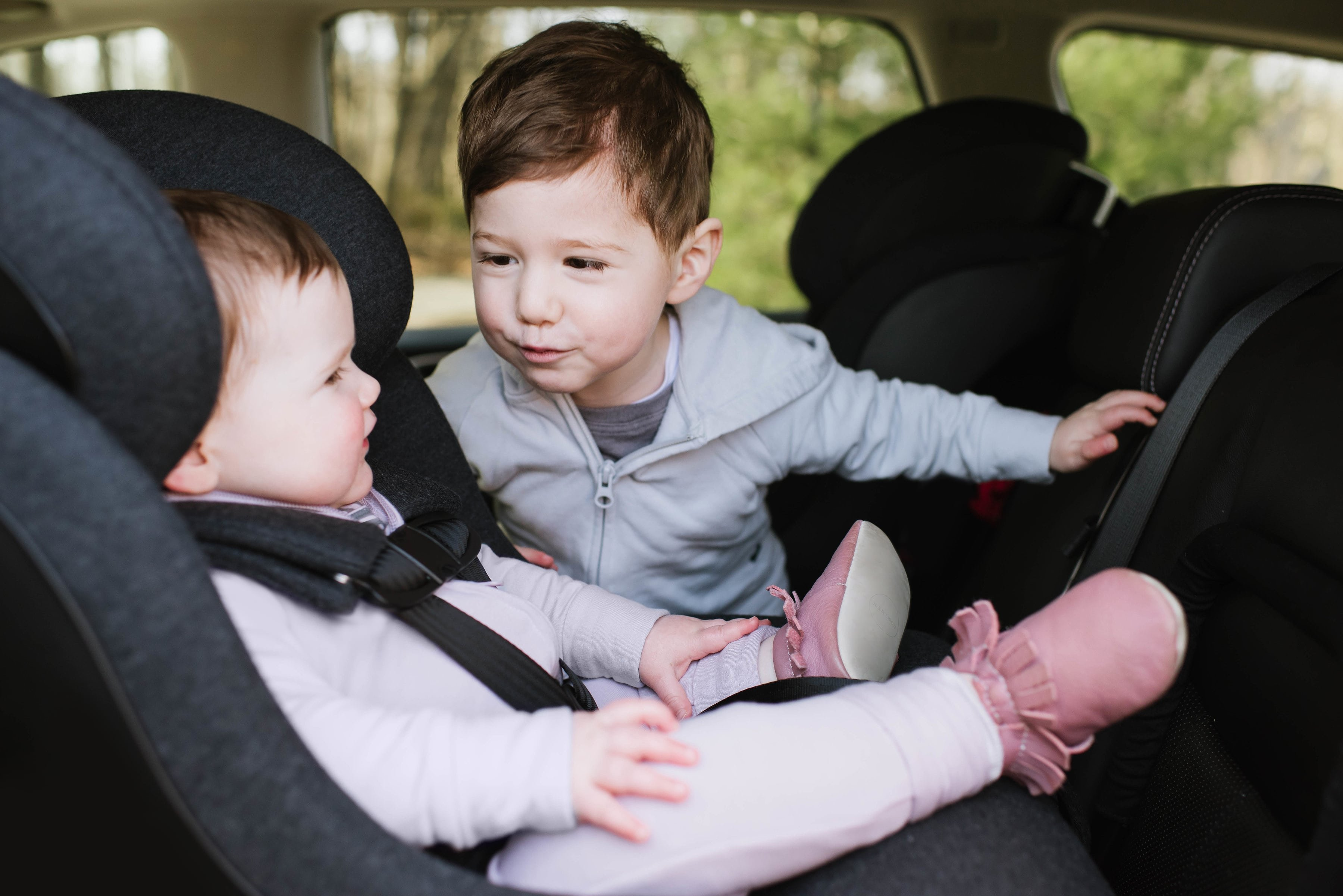 Baby sitting in Clek Mammoth Infant Car Seat while older brother sits beside her
