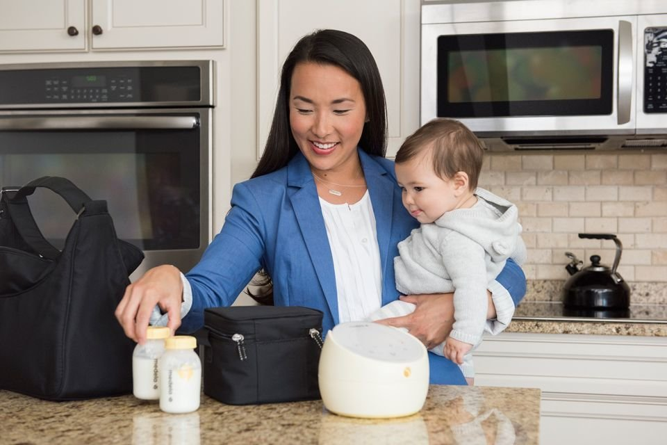 Mom with Medela breast pump kit and breast milk bottles holding baby in kitchen