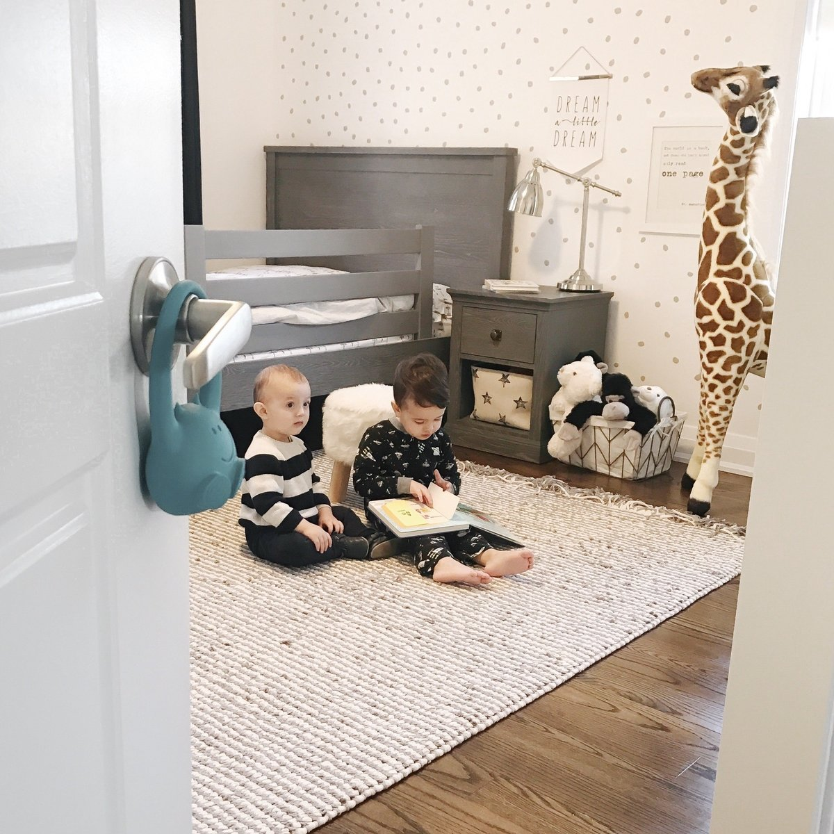 Two young boys reading together in bedroom with DECCO Toddler Monitor on doorknob