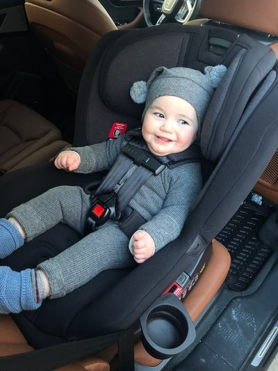 Happy Baby Smiling While SItting in Nuna Rava Car Seat Installed in Car
