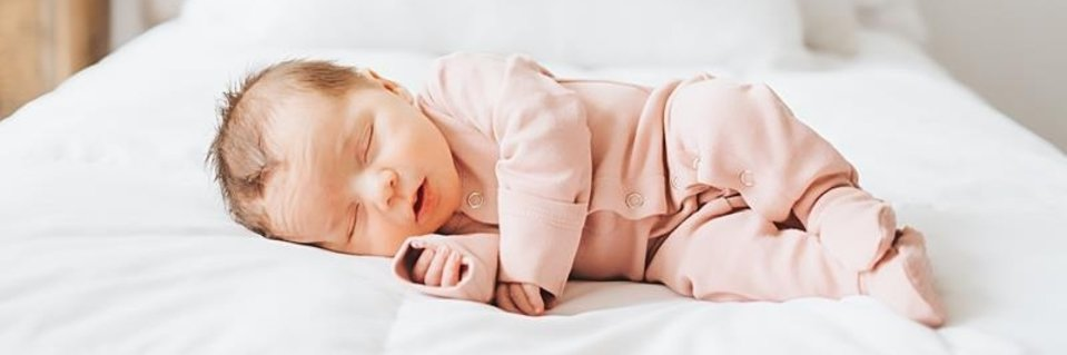 Baby sleeping in a blush onesie from L'ovedBaby