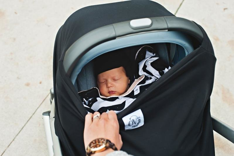 Newborn in car seat with The oVer Company car seat cover
