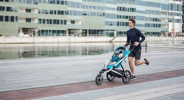 Man running with baby in a Thule Urban Glide 2 Single Stroller in Thule Blue with Silver Flame