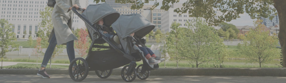 Woman pushing Baby Jogger double stroller with two kids through park in the city
