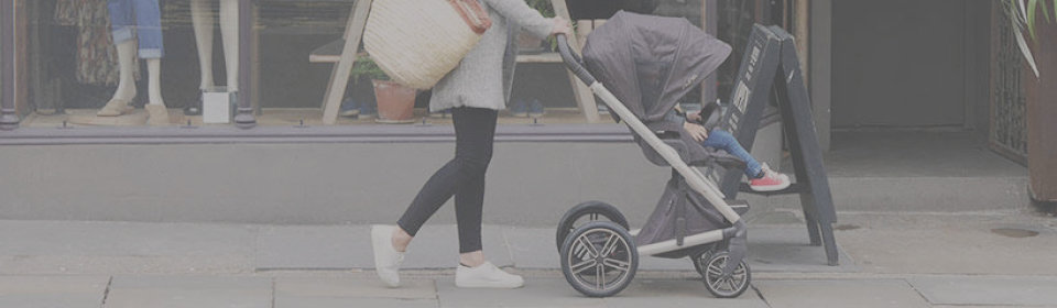 mom pushing nuna stroller with baby on a sidewalk past a clothing store