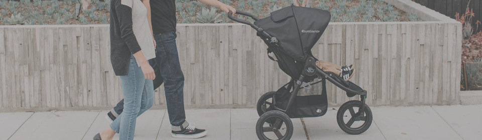 Couple walking down the street pushing Bumbleride stroller