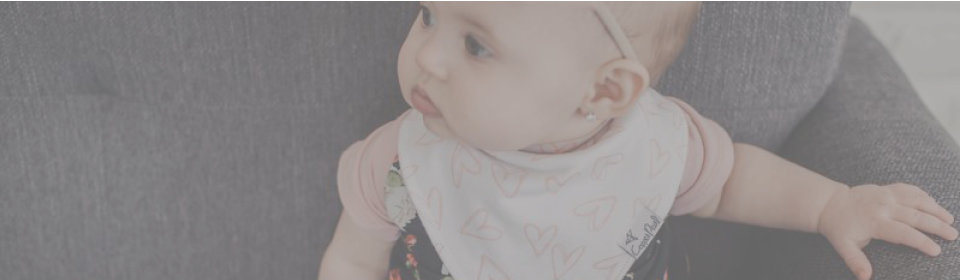 Baby girl wearing Copper Pearl bib with pink hearts design