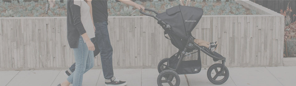 Couple in jeans pushing Bumbleride stroller down the street