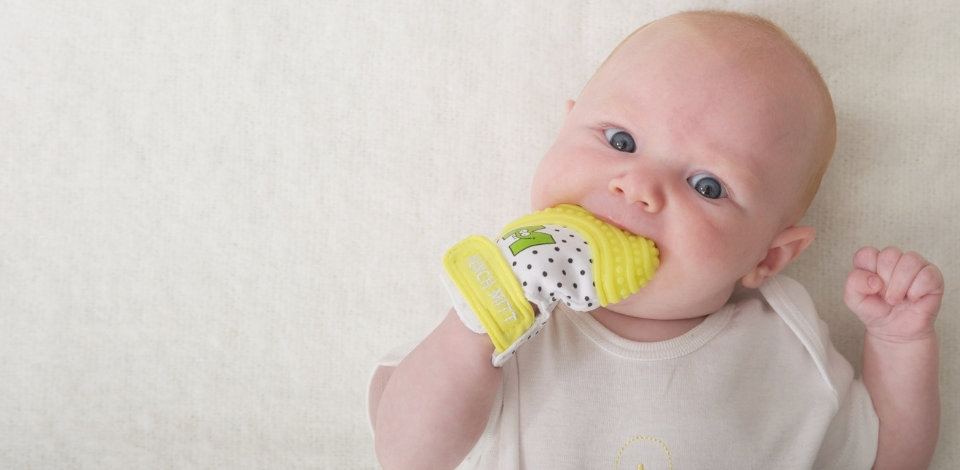 Teething baby chewing on yellow munch mit
