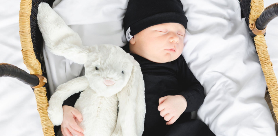Baby wearing black hat from OVer Company snuggling with Bashful Bunny White from JellyCat in Bassinet