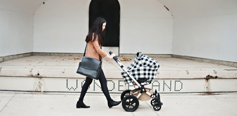 Woman in tan jacket pushing stroller with black and white buffalo check car seat cover