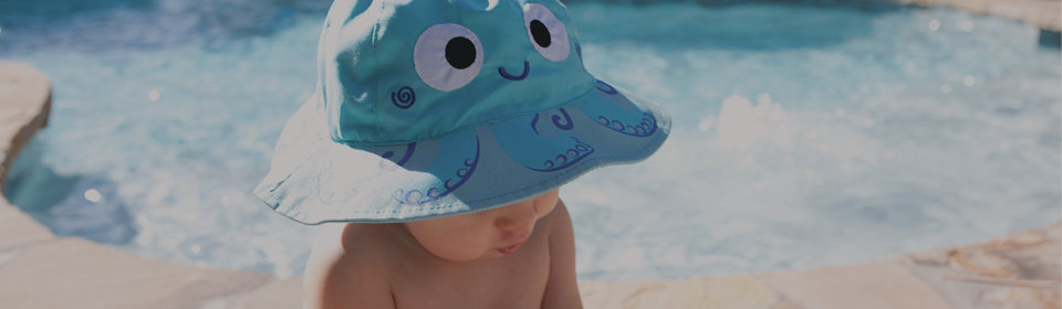 Baby near pool wearing blue sun hat with octopus design