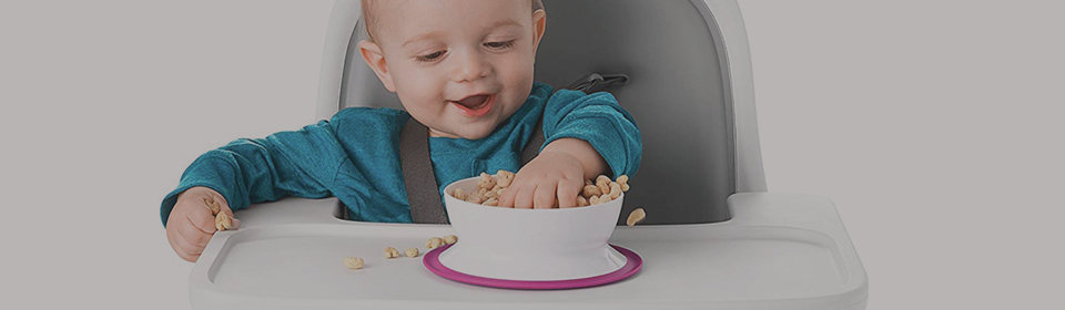 Little boy in the OXO Tot Sprout high chair eating out cereal out of a Suction Bowl