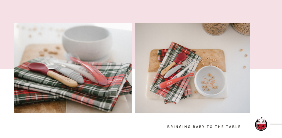 Collection of baby and children's cutlery shown on cutting board with bowl and plaid napkins