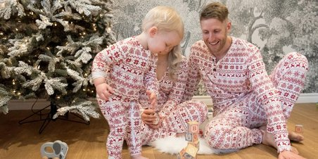 Family in matching pajamas playing with toys thumbnail