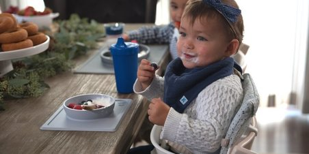 Baby sitting in tripp trapp high chair eating berries thumbnail