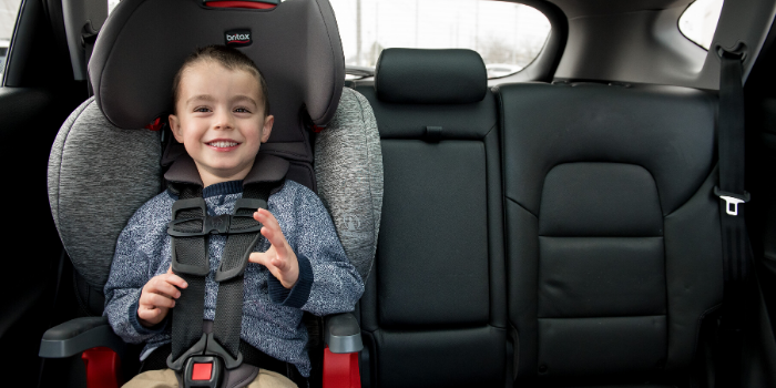 Child riding in Britax Car Seat in back of car with black leather seats