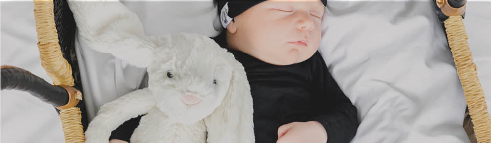 Little baby sleeping holding a Jellycat plush toy bunny