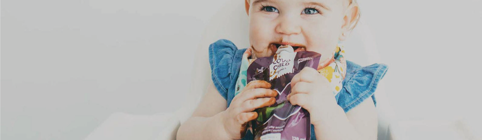 Little girl eating puree love child organic pouch