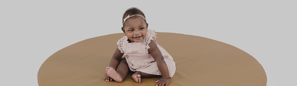 Little girl sitting on a Gathre leather circle playmat