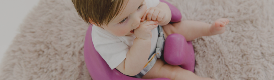 Little girl sitting in a Bumbo floor seat