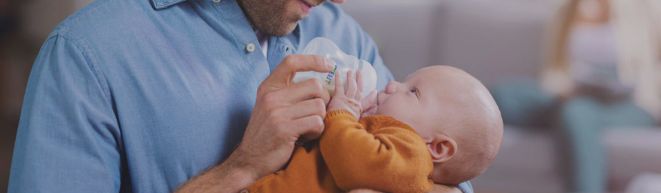 Father feeding baby with Avent baby bottle