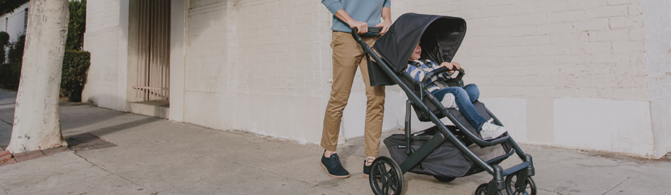 Dad pushing son in UPPAbaby CRUZ V2 stroller down the street