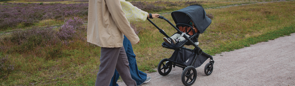 Parents pushing Bugaboo Fox2 stroller down the road