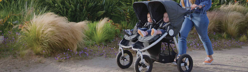 Mother pushing twins in a Bumbleride Indie Twin double stroller