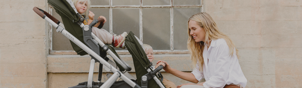 Mom bending down to check on her 2 kids in a UPPAbaby VISTA V2 with second seat