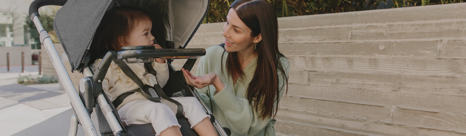 Mom giving child snacks on snack tray in a UPPAbaby VISTA stroller
