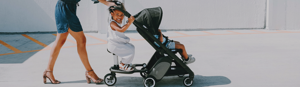 Mom pushing baby in a Bugaboo Ant stroller with child sitting on stroller board