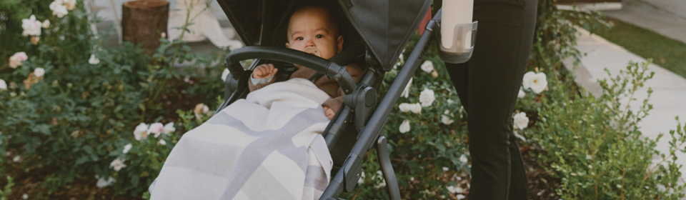 Mother pushing little boy in an VISTA stroller with an UPPAbaby stroller blanket over him