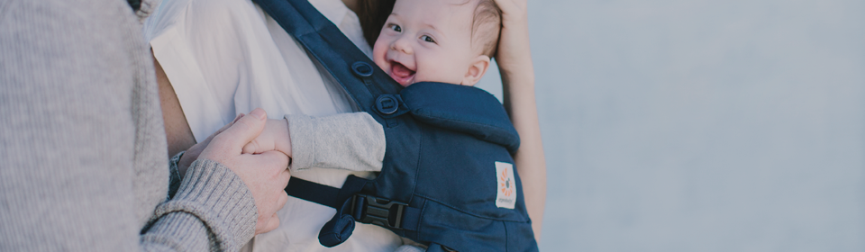 Mom using ERGOBaby carrier to carry smiling baby while husband holds his hand