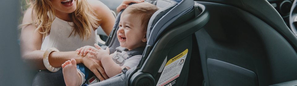 Little boy smiling in the Bryce white UPPAbaby MESA infant seat