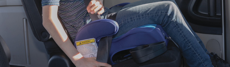 Boy putting his seatbelt on while sitting in a blue Diono Solana Backless Booster Seat