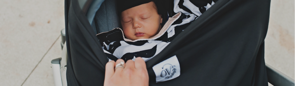 Baby sleeping in UPPAbaby MESA infant seat covered in an Over Company Black Car Seat Cover
