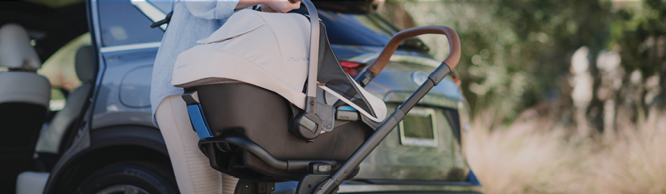 Mother making a travel system by putting a Nuna PIPA infant seat on Nuna MIXX stroller