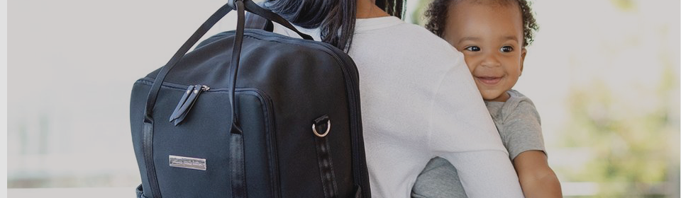 Petunia Pickle Bottom Inter-Mix diaper bag on mom's shoulder while holding baby